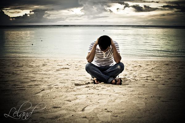 man on beach in pain