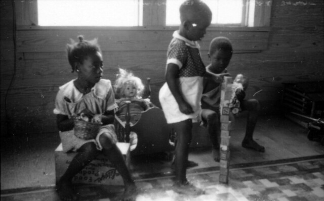 Three black children playing with dolls and alphabet blocks at Delta ...