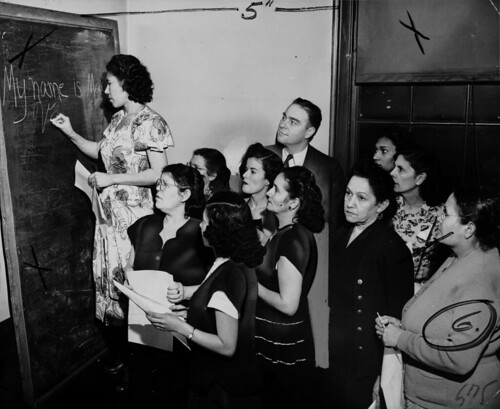 Maria Vargas writes her name on the blackboard during ILGWU Local 91's English class for Spanish-speaking members, taught by William Waens.