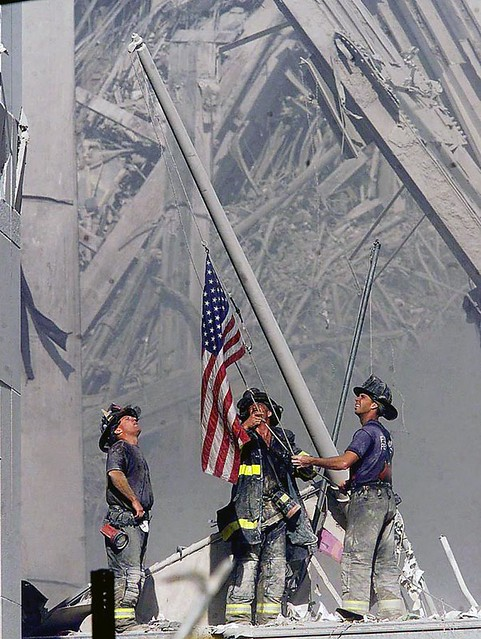 Brooklyn firefighters George Johnson, left, of ladder 157, Dan McWilliams, center, of ladder 157, and Billy Eisengrein, right, of Rescue 2, raise a flag at the World Trade Center in New York, by Thomas E. Franklin
