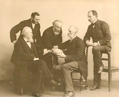 A group photo of Sir William Macewen (1848-1924) with Adolph Barkan (1845-1935), Stanley Stillman (1861-1935), Levi Cooper Lane (1828-1902),  Joseph Oakland Hirschfelfer (1854-1920) demonstrating Macewen's triangle