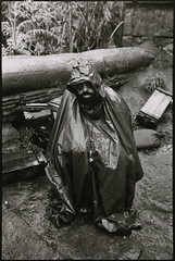 Francis Ford Coppola sheltering himself from the driving rain on the set of Apocalypse Now that added to the troubles of an already beleaguered shoot, by Mary Ellen Mark 1979