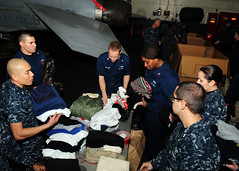 PACIFIC OCEAN (March 18, 2011) Sailors aboard the aircraft carrier USS Ronald Reagan (CVN 76) organize clothing donated by the crew of Ronald Reagan for displaced Japanese citizens. (U.S. Navy Photo by Mass Communication Specialist 2nd Class Josh Cassatt/Released)