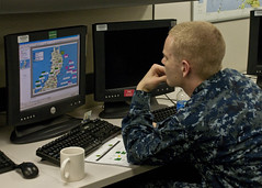 YOKOSUKA, Japan (March 25, 2011) Aerographer's Mate 3rd Class Nick Pennell, a watch stander at the Naval Oceanography and Anti-Submarine Warfare Center, looks over a Japan Self-Defense Force Mobile Operations sheet at Commander Fleet Activities Yokosuka (CFAY). (U.S. Navy photo by Mass Communication Specialist 3rd Class Mikey Mulcare)