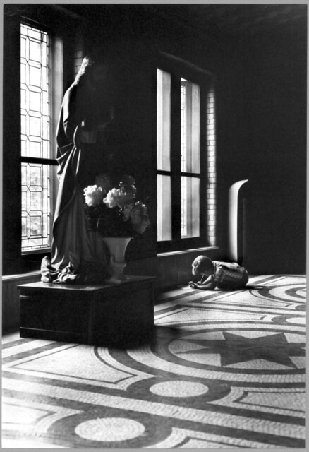Boy writing on paper in window-lit hallway with Christ figure, St. Joseph's School for the Deaf, by William Gedney c.1960