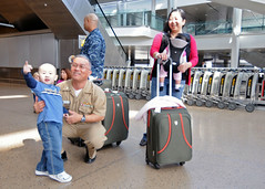 SEATTLE (March 23, 2011) Cmdr. Manuel Biadog, Jr., Naval Base Kitsap command chaplain, entertains a child while his mother waits for her luggage at Seattle International Airport after arriving from Japan. (U.S. Navy photo by Mass Communication Specialist 2nd Class Nathan Lockwood)
