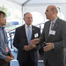 Ismael Agasino, of Bauer, Inc., talks with State Senator Henri Martin and State Representative Selim Noujaim during a 100th anniversary celebration of the company at their Bristol, CT headquarters.
