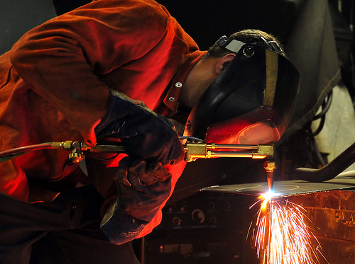Sailor arc-welds a flange aboard USS Pearl Harbor.
