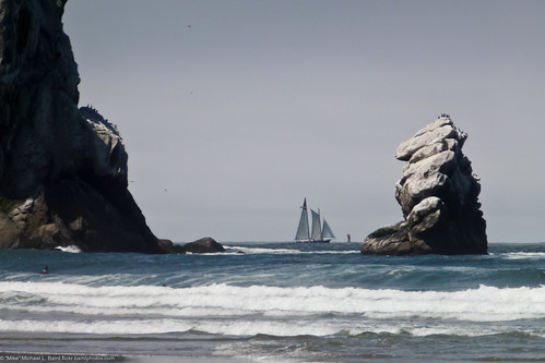 Old style sail ship sails inside a buoy, between Morro Rock (Left) and Pillar Rock (Right) off Morro Strand State Beach