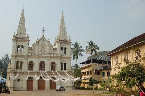 Zweistöckige Basilika in weiß mit zwei Türmen. Der Eingang ist mit weissen Sterngirlanden geschmückt.