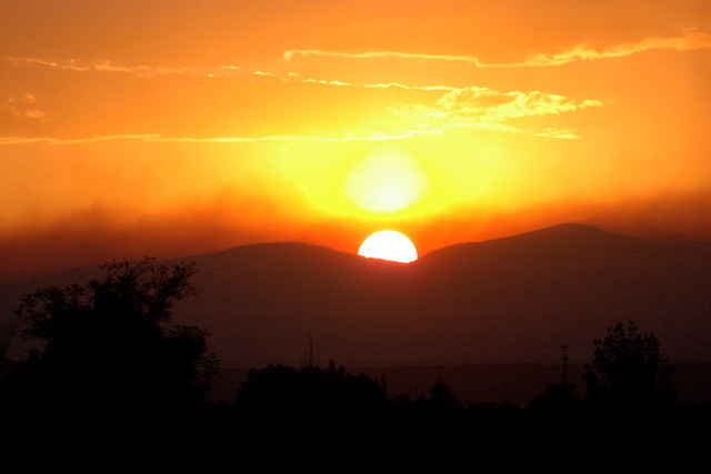 The Sun descends behind Los Alamos and the Jemez Mountains as seen from Santa Fe--Thursday evening, June 30.  Photo by Jeff Berger