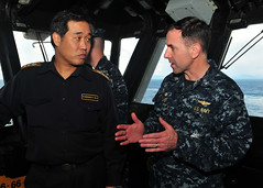 PACIFIC OCEAN (March 27, 2011) Capt. David Fluker, commanding officer of the forward-deployed amphibious assault ship USS Essex (LHD 2) discusses ship capabilities on the Essex bridge with Japan Maritime Self-Defense Force Rear Adm. Hiroyuki Kasui, commander, Escort Flotilla 1. (U.S. Navy photo by Mass Communication Specialist 2nd Class Casey H. Kyhl)