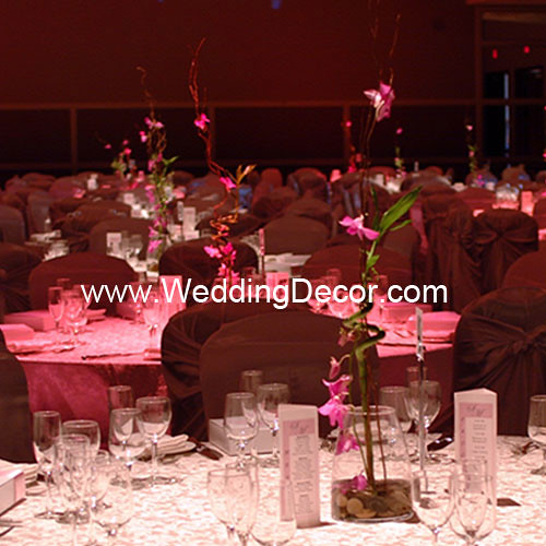 A wedding centerpiece with fuchsia orchids curly willow bamboo and rocks