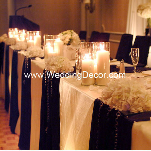 Head table decorations for a wedding reception in black and ivory with