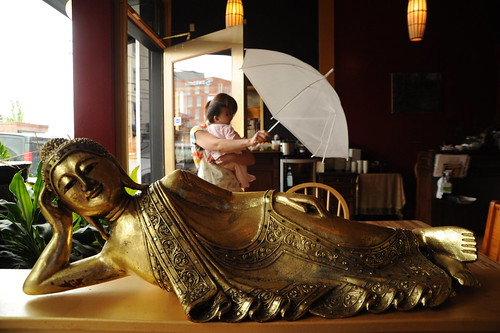 Reclining gold Thai Buddha, Sky Blue, a baby, enters with her friend carrying an auspicious white umbrella, UMA Thai restaurant, Ballard, Seattle, Washington, USA by Wonderlane