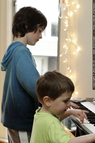 cousins playing a piano duet