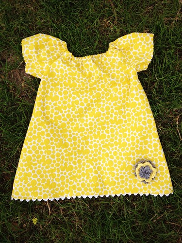 Infant peasant dress with crochet flower embellishment