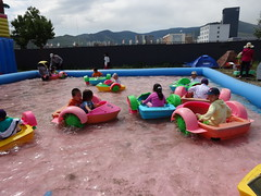 tubing(0.0), playground slide(0.0), amusement park(0.0), outdoor play equipment(1.0), vehicle(1.0), play(1.0), recreation(1.0), outdoor recreation(1.0), leisure(1.0), water park(1.0), inflatable(1.0), playground(1.0),