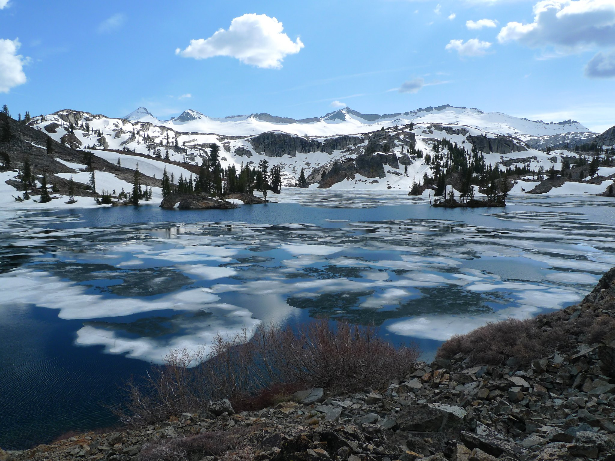 Heather Lake has some ice on it. The peaks of the Crystal Range behind are still blanketed in snow.