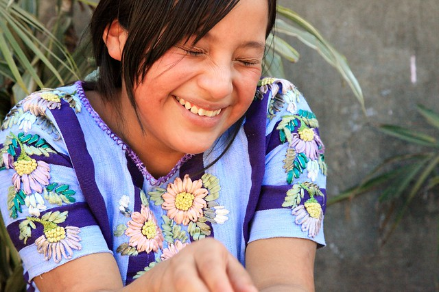 Laughing Tz'utuhil Maya Girl with traje, huipil, at a school in Panabaj, Guatemala