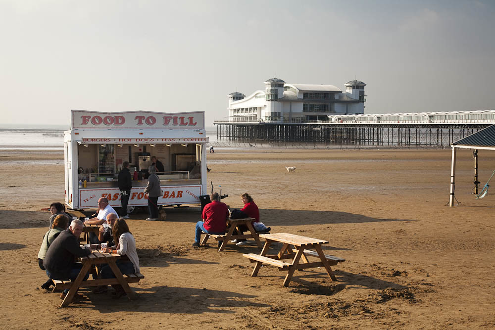 People eating and drinking at a fast food van on the beach along the seafront at Weston-Super-Mare, Somerset, Uk