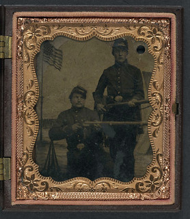 [Brothers William and Philip J. Letsinger of Company D, 14th Indiana Regiment posing with rifles in front of Camp Michigan painted backdrop] (LOC)