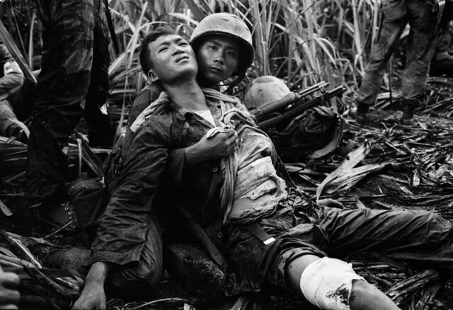 A South Vietnamese Marine, severely wounded in a Viet Cong ambush, is comforted by a comrade in a sugar cane field at Duc Hoa, by Horst Faas 1963
