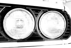 automotive tail & brake light(0.0), wheel(0.0), rim(0.0), city car(0.0), automotive exterior(1.0), automotive lighting(1.0), automotive design(1.0), light(1.0), monochrome photography(1.0), grille(1.0), bumper(1.0), headlamp(1.0), monochrome(1.0), black-and-white(1.0), lighting(1.0),