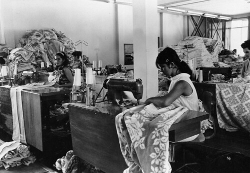 Women working at sewing machines with stacks of fabric and finished garments piled around them, 1970