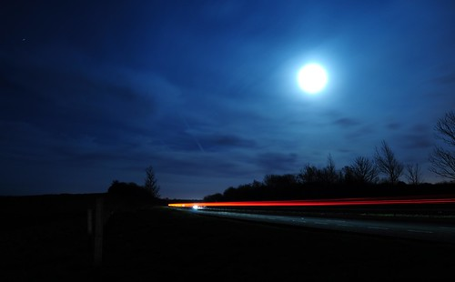 Light trails of cars with the moon