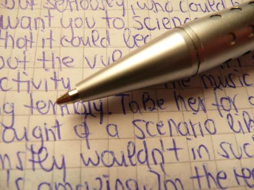 Metallic ballpen tips / biro Ballpen Ballpoint pen in silver with handwritten random blue text on quad-ruled paper
