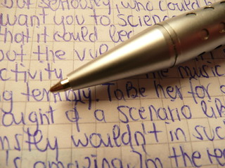 Metallic ballpen tips / biro Ballpen Ballpoint pen in silver with handwritten random blue text on quad-ruled paper