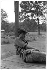 Young man sitting on a porch, leaning against a pole, Kentucky, 1971, by William Gedney