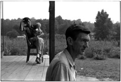 Profile of Willie Cornett looking out from his porch, a son holding a grandson sitting on a chair behind him, Kentucky, 1971, by William Gedney