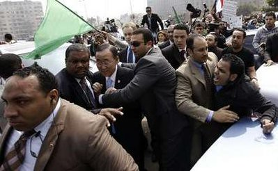 United Nations Secretary General Ban Ki-moon is shielded by guards after coming under attack by demonstrators opposing the imperialist bombing of Libya which was justified by Security Council action. by Pan-African News Wire File Photos