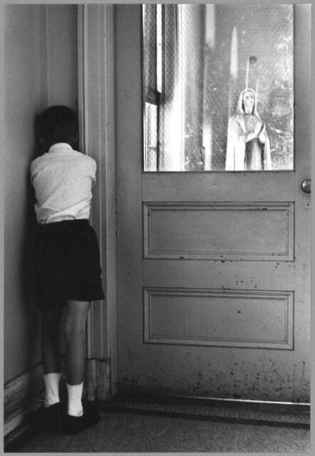 Student facing corner next to a door. Statue of Mary appears through window, St. Joseph's School for the Deaf, by William Gedney c1960