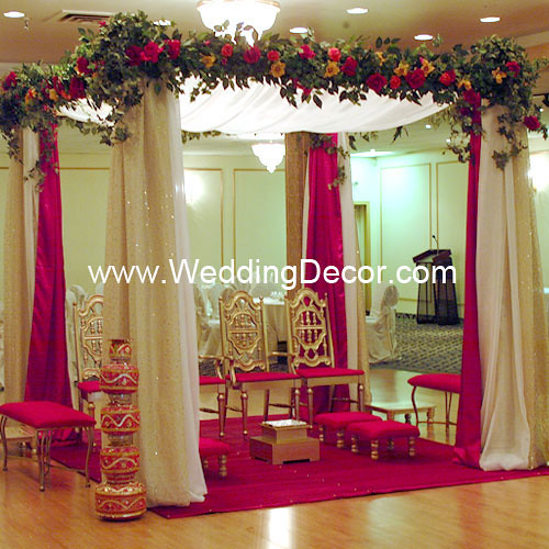 A wedding mandap in red and ivory with gold sparkle accets and silk floral