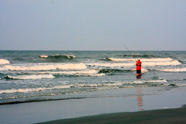 Surf fishing in the early morning sunrise at sunset beach for North carolina surf fishing license