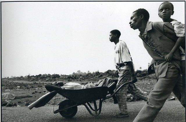 A Rwandan refugee family walks to a relief center at Goma, Zaire, using a wheelbarrow to transport a member of the family who is dying of cholera, by David Turnley 1994