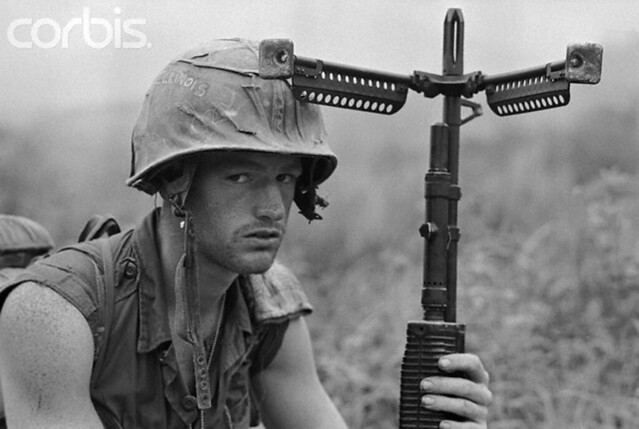 South Vietnam, 1968, an American soldier keeps a wary eye on the hills and a firm hand on his weapon after U.S. forces captured Hill 471 along Highway 9 during