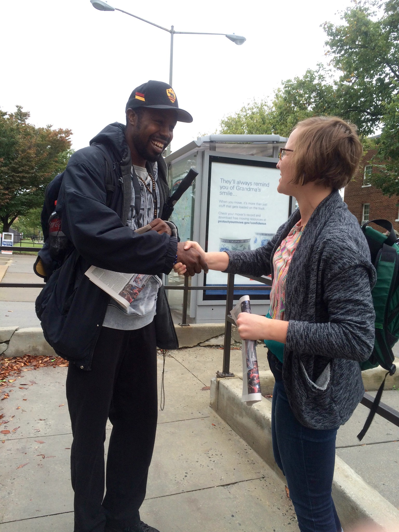 A man in a blue coat and baseball cap shakes hands with a woman, who we only see in profile. They are standing on an urban sidewalk in front of a bus shelter.