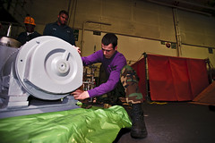 PACIFIC OCEAN (March 29, 2011) Aviation Boatswain's Mate (Fuel) 3rd Class Richard Bell removes mounting bolts from the base of a JP-5 fuel filtering unit in the hangar bay aboard the aircraft carrier USS George Washington (CVN 73). This step is essential in preparing the 4,000lb fuel filter prior to lowering it from the hangar bay to the seventh deck below. (U.S. Navy Photo by Mass Communication Specialist 3rd Class Juan Manuel Pinalez Jr.)