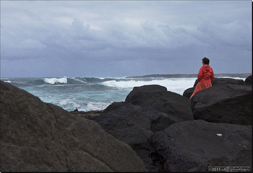 Mujer en rojo sobre rocas negras mirando olas y nubes   Woman in red over black rocks watching waves and clouds Donna in rosso su rocce nere osserva onde e nubi