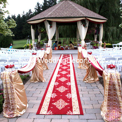 A wedding mandap in ivory and gold with a red aisle runner and piller