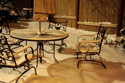 Soft sculptural quality of winter snow, patio, front yard, curvy metal patio chairs and table under snow, umbrella fabric, shadows, bamboo fence, Broadview, Seattle, Washington, USA by Wonderlane