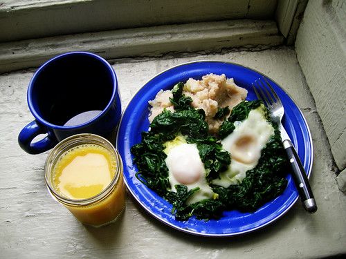 fried eggs in spinach over mashed potatoes and cannellini beans with coffee and OJ