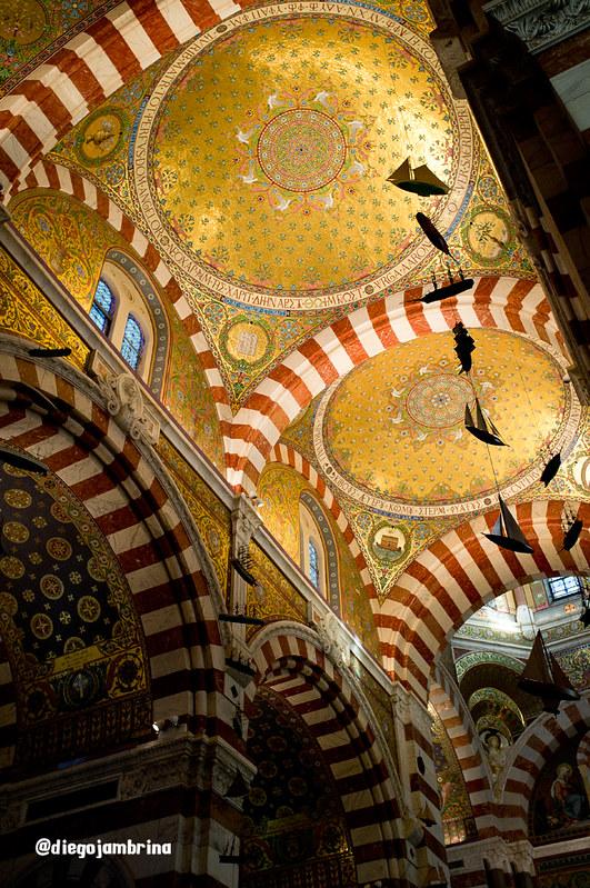 Los barcos cuelgan del techo colorido de Notre Damme de la Garde