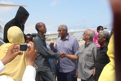 Somalis deported from Kenya are greeted by Minister for Transport and Air Travel Said Jama Qorshel (blue shirt), Minister for Foreign Affairs Buri Mohamed Hamza (shaking hands with deportee) and the director of Somali Immigration Department, General Abdul