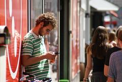 Jongen met zonnebril bekijk z'n mobiel