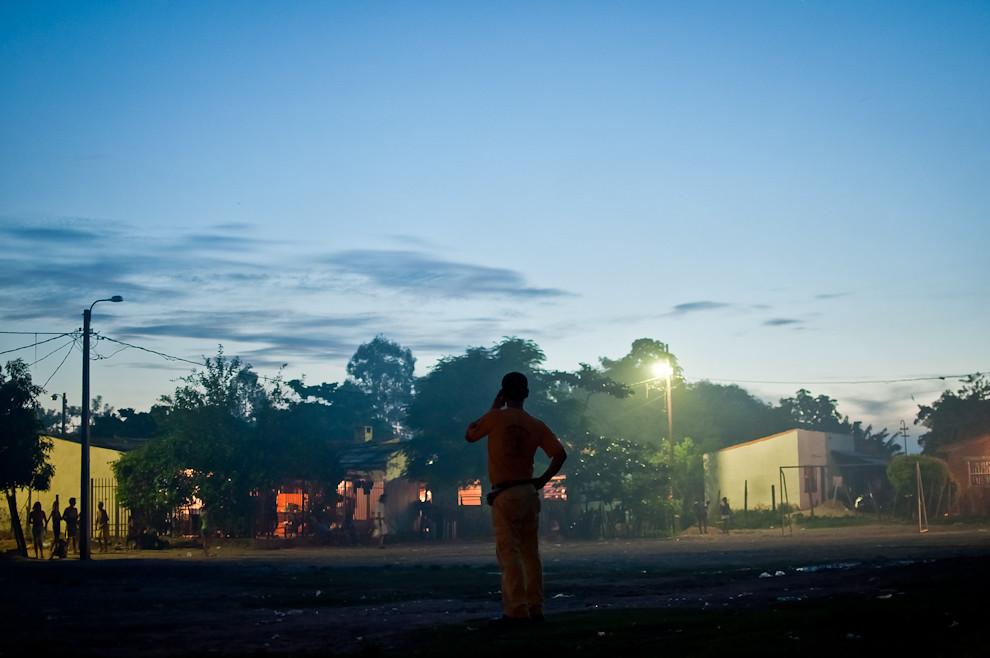 Un bombero se comunica por teléfono mientras estaban atendiendo a un herido en una precaria casa en el barrio Tacumbú de Asunción. El servicio de esa tarde fue ordenado por la central 132 para atender a un chico lastimado por una caída de altura que tuvo que ser derivado a urgencias médicas. (Elton Núñez)